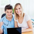 Portrait of a cheerful couple using a laptop sitting together at - Stok fotoğraf