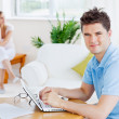 Happy man using his laptop sitting at a table with his girlfrien — Stock Photo #10837791