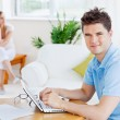 Stock Photo: Happy musing his laptop sitting at table with his girlfrien
