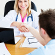 Friendly female doctor shaking hands with patient sitting in her — Stock Photo #10837801