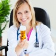 Attractive female doctor showing pills to the camera sitting in — Stock Photo