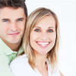 Adorable couple smiling at the camera and standing against a whi — Stock Photo