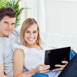 Young happy couple lying on the sofa with laptop smiling at the — Stock Photo #10837848