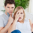 Scared couple watching a horror movie lying on the sofa at home — Stock Photo