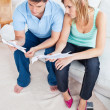 Young caucasian couple looking at bills sitting on the sofa — Stock Photo #10837887