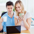 Happy couple using a laptop sitting together at a table holding - Foto de Stock