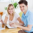 Gorgeous couple working together on the laptop sitting at a tabl — Stock Photo
