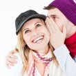 Handsome man with hat telling a secret to his laughing girlfrien — Stock Photo #10837964