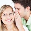 Young man whispering something to his attentive female friend — Stock Photo #10837977