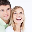 Portrait of a joyful couple looking at the top standing against — Stock Photo