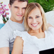 Portrait of a young caucasian couple with laptop relaxing on the — Stock Photo #10837982