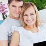 Portret van een jonge Kaukasische paar met laptop ontspannen op de — Stockfoto #10837982