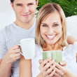 Lovely couple resting on the sofa holding cups of coffee — Stock Photo