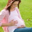 Royalty-Free Stock Photo: Adorable pregnant woman sitting on the grass touching her belly