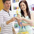 Young caucasian couple buying shampoo standing in a department o — Stock Photo
