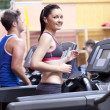 Athletic woman listening to the music while using a treadmill in — Stock Photo
