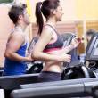 Pretty woman with earphones using a treadmill with her boyfriend — Stock Photo