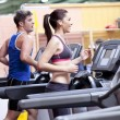 Healthy couple running on a treadmill in a sport centre — Stock Photo #10838044