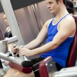 Serious athletic man using a leg press in the weights room of a — Stock Photo #10838076