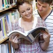 Two students enjoying reading a book together in the library — Stock Photo