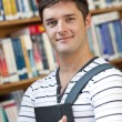 Portrait of a smart student holding a book standing in the libra — Stock Photo #10838079