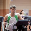 Handsome man doing exercises using cross trainer in a fitness ce — Stock Photo #10838086