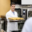Stock Photo: Young baker holding baguettes and breads standing in the kitchen