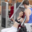 Sporty woman sitting on a shoulder press talking with her coach — Stock Photo