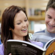 Stock Photo: Cheerful couple reading book in science department of bo