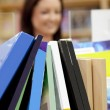 Stock Photo: Close-up of book shelf in library with female customer in th