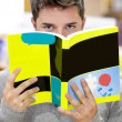 Stock Photo: Male student standing in book shop hiding his face behind bo