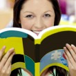 Portrait of a beautiful woman holding a book in a library smilin — Stock Photo #10838140