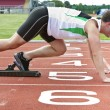 Stock Photo: Handsome sprinter on starting line putting his foot in s