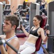 Stock Photo: Concentrated couple using shoulder press in fitness centre