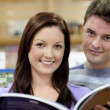 Portrait of a cute couple reading a book in a shop — Stock Photo #10838153