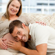 Smiling future dad listening to the belly of his wife sitting on — Stock Photo