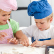 Foto Stock: Young brother and sister kneading a dough to make cakes