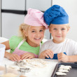 Portrait of two adorable children baking in the kitchen — Stockfoto