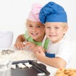 Two little chefs preparing cookies in the kitchen — Stock Photo