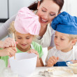 Mother with her children baking together in the kitchen — Stock Photo