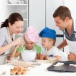 Adorable family baking together in the kitchen - Stock Photo