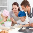 Happy family cooking a cream together in the kitchen — Stock fotografie #10838522