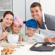 Portrait of a joyful family cooking littles cakes — Stockfoto