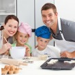 Portrait of a joyful family cooking littles cakes — Foto de Stock