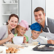 Parents and childrnbaking together in the kitchen — Stock Photo