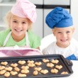 Happy little brother and sister with their biscuits ready to eat — Stock Photo #10838533