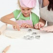 Cute daughter and her beautiful mother making cookies using baki — Stock Photo #10838540