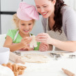 Cheerful mother and daughter making cookies in form of a man — Stock Photo #10838547
