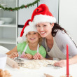Portrait of a cute girl with her mother baking Christmas cookies — Stock Photo #10838552