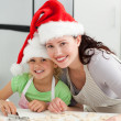 Stock Photo: Beautiful mother and daughter cooking Christmas biscuits
